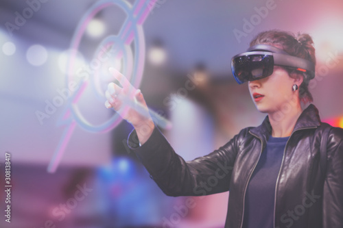 Portrait of young Caucasian woman using augmented and virtual reality with holographic hololens glasses Wallpaper Mural
