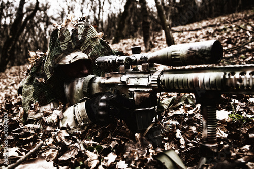 Army sniper hiding on ground in forest leaves Wallpaper Mural