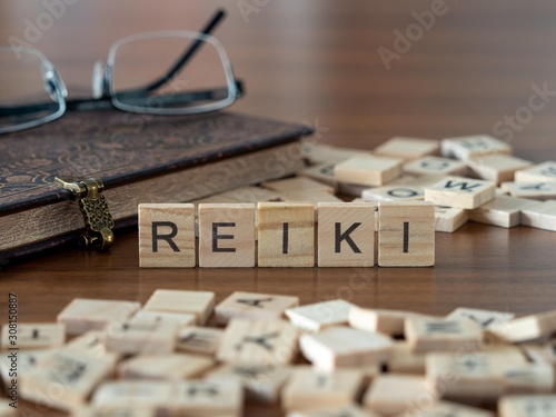 Photo reiki the word or concept represented by wooden letter tiles