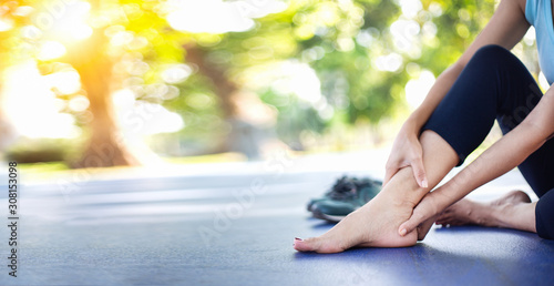 Young women have pain in the ankle while exercising in a concrete path in the park Wallpaper Mural