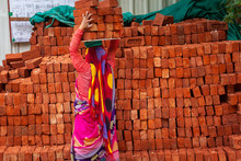 A Woman Carrying Bricks On Her...