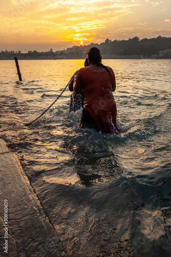 Photo Two woman taking a dip in river Ganga at sunset