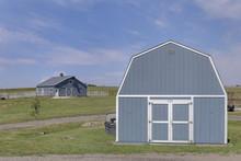 Two Grey Barns With White Trim