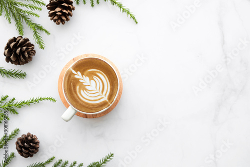 Photographie White marble table with cup of latte coffee and Christmas decoration with pine branches and pine cones