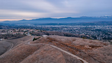 Aerial View Of Open Rolling Hills In Suburban Southern California.  Radio Tower Atop Hill During Sunset Surrounded By Mountains And Ocean