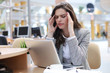 Frustrated business woman looking exhausted while sitting at her working place