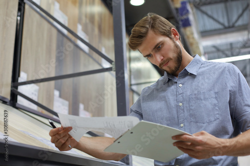 Foto Young man shopping or working in a hardware warehouse standing checking supplies on his tablet