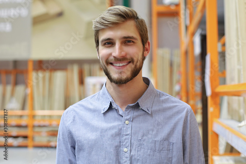 Fototapety, obrazy: portrait of a smiling young warehouse worker working in a cash and carry wholesale store.