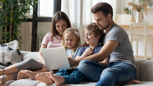 Married couple and kids using laptop having fun in internet - 308191092