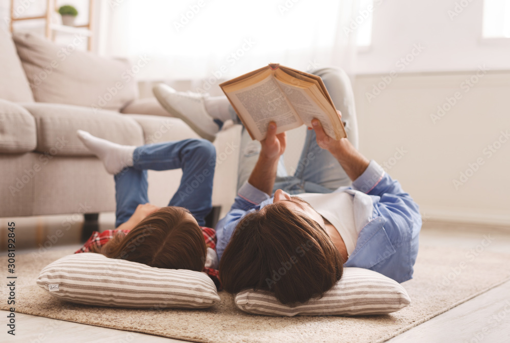 Fototapeta Little girl and father enjoying book together, laying on floor