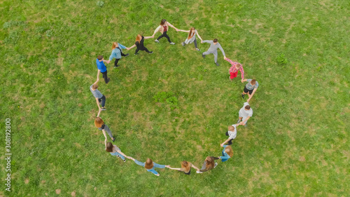 Obraz Friends in a circle holding hands make a round dance in the field. - fototapety do salonu