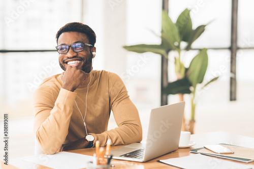 Smiling black worker in glasses listening to music Wallpaper Mural