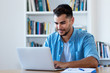 Handsome mexican hipster man sending email with laptop
