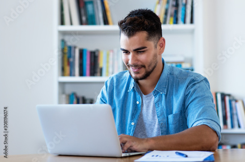 Fotomural Handsome mexican hipster man sending email with laptop