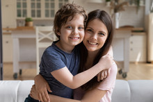 Seated On Couch At Home Young Mother Embracing Preschool Son