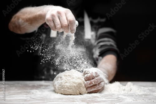 White flour flies in air on black background, pastry chef claps hands and prepar Wallpaper Mural