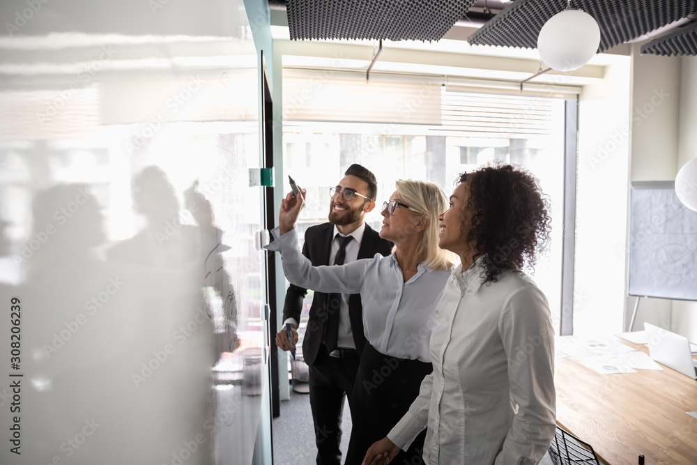 Fototapeta Motivated diverse employees brainstorm develop strategies on whiteboard