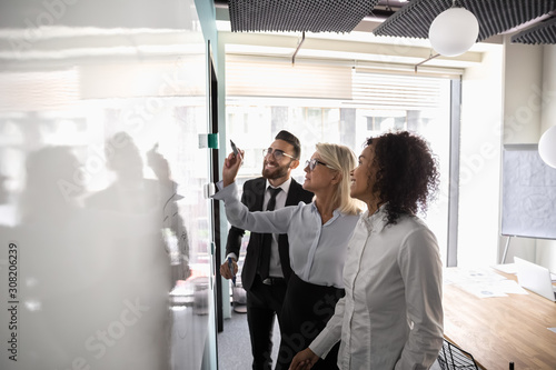 Motivated diverse employees brainstorm develop strategies on whiteboard