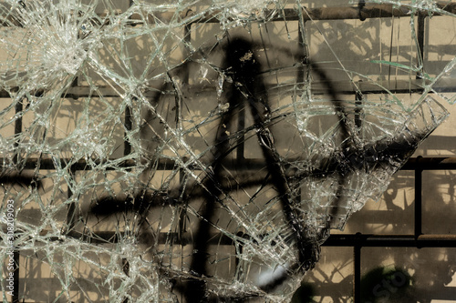 Photo Anarchy symbol painted on cracked glass of a broken shopping window
