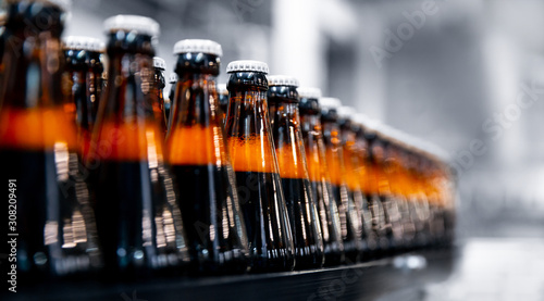 Fototapeta Glass bottles of beer on dark background with sun light. Concept brewery plant production line obraz