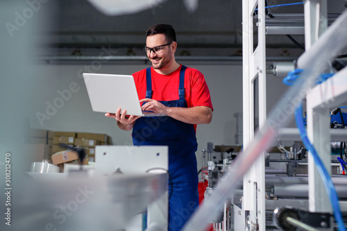 Fototapety, obrazy: Engineer in the factory using laptop computer for maintenance.
