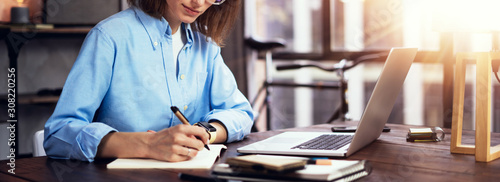 Young woman working with a laptop. Female freelancer connecting to internet via computer. Blogger or journalist writing new article.