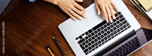 Closeup photo of female hands with a laptop. Female freelancer connecting to internet via computer. Blogger or journalist writing new article.