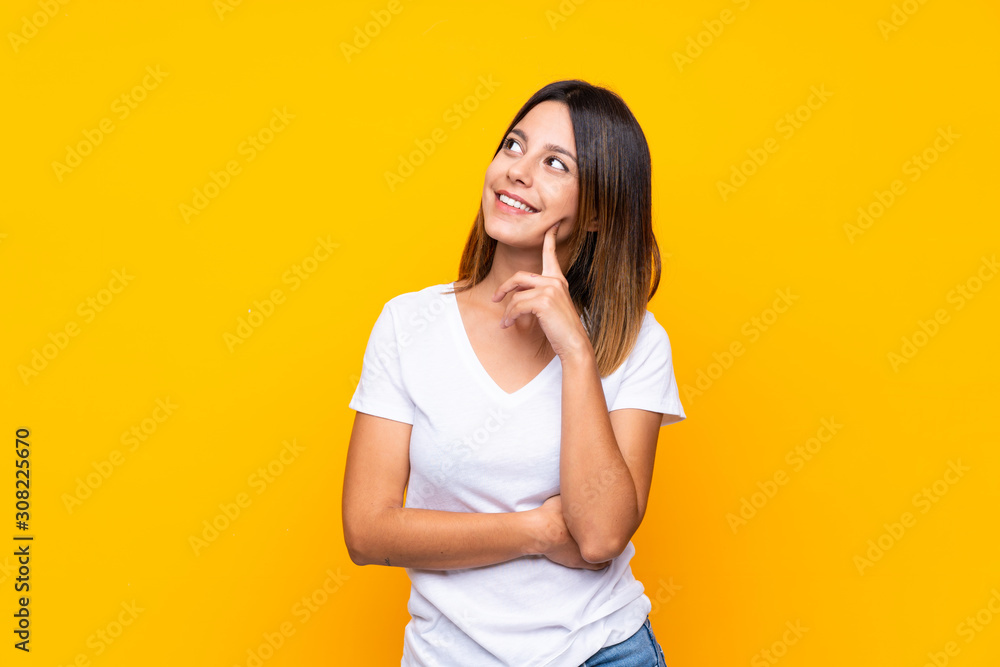 Fototapeta Young woman over isolated yellow background thinking an idea while looking up