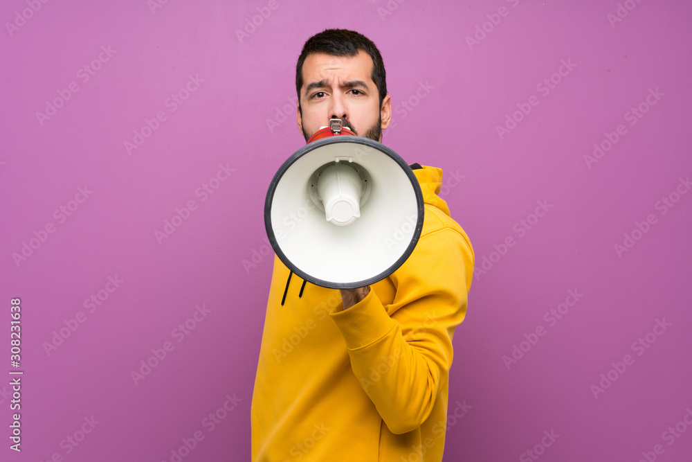 Fototapeta Handsome man with yellow sweatshirt shouting through a megaphone
