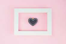 White Frame, Black Wooden Heart Pin On Pink Background. Invitation, Card Concept. Top View, Copy Space, Flat Lay, Mock Up