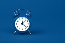 Close Up One Classic Alarm Clock Over Blue Background