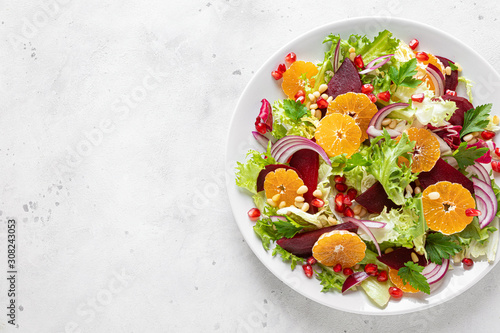 Fotografía  Christmas salad with boiled beet, red onion, tangerines, pomegranate, parsley, p