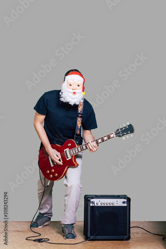 Man in Santa mask and casual сlothing playing electric guitar isolated on grey background Wallpaper Mural