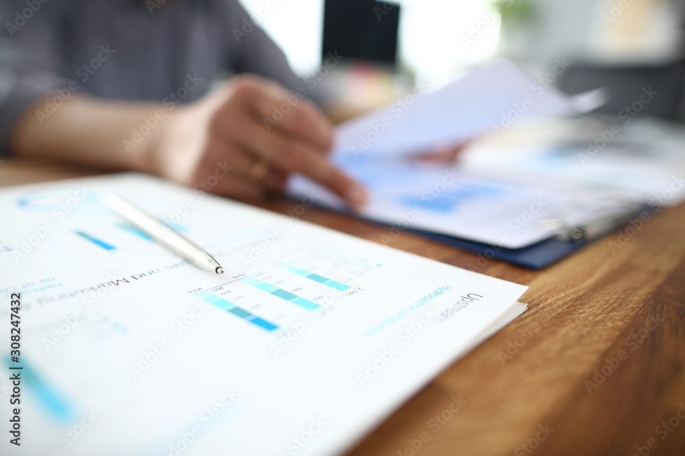 Fototapeta Close up of male employee read paper handout material during office meeting, man analyzing paperwork report at briefing.