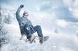 Leinwanddruck Bild - Happy man sledding down a slope in winter