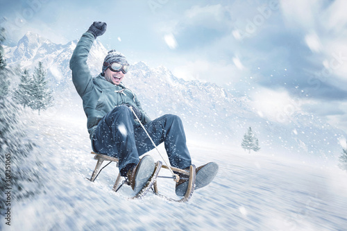 Happy man sledding down a slope in winter