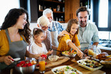 Grandparents, parents and children spending happy time in the kitchen