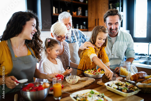 Grandparents, parents and children spending happy time in the kitchen - 308257620