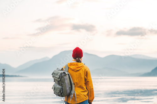 Obraz Back view of male tourist with rucksack standing on coast in front of great mountain while journey.  Man traveler wearing yellow jacket with backpack explore scandinavia nature. Wanderlust outdoor - fototapety do salonu