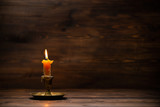 burning old candle with vintage brass candlestick on wooden background in minimalist room interior with copy space