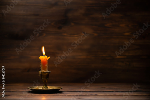 Obraz na plátne burning old candle with vintage brass candlestick on wooden background in minima