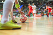 Futsal match - close up of ball in the corner and player's hand and legs.