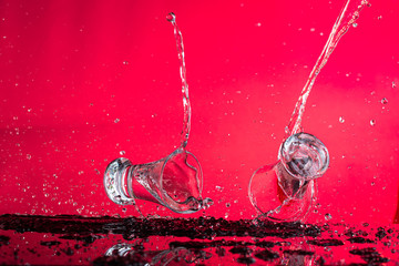 two falling glasses with vodka in motion are frozen with a spray and a splash