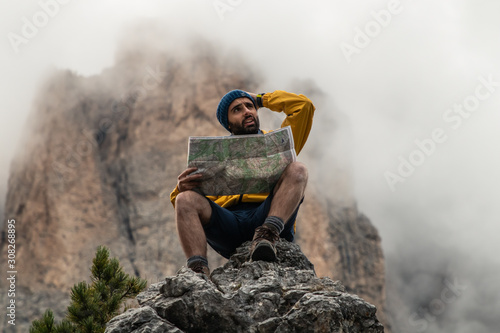 Fototapeta Young man hiker sitting on stone mountain reading map, with cloudy sky and fog. Yellow jacket, backpack, black beard and beanie. Traveling dolomites, Italy. obraz