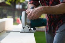 Carpenter Using Circular Saw Cutting Wooden Boards