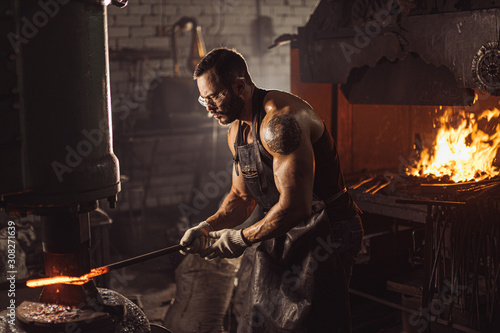 Vászonkép Young forger shaping metal on a jackhammer in the blacksmith workshop, wearing leather uniform