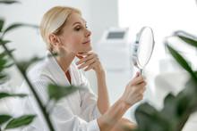 Smiling Pretty Woman Using Mirror In Spa Center