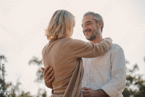 Obraz Older Lover and dating concept.Beautiful Senior couple romantic dancing in park.mature couple in summer park.Elderly man and old woman in love dancing outdoors. - fototapety do salonu