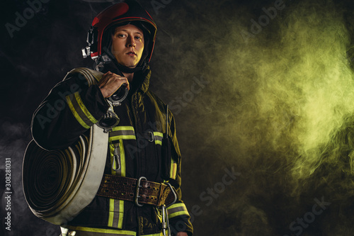 Photo brave extinguisher or fireman dressed in dark protective suit uniform, with helm