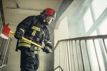 Young Firefighter With Hammer Go To Save And Protect Wearing Uniform, On The Landing